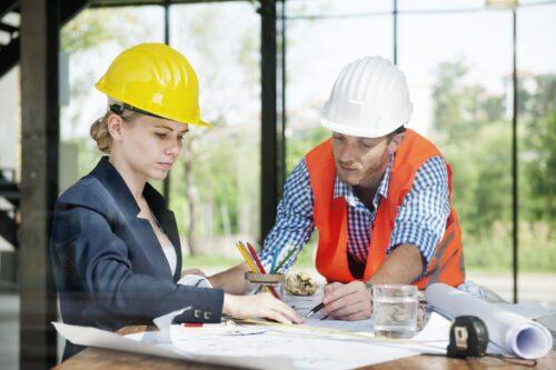 homme et femme dans le domain de la construction qui révise des plans